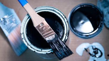 A close look at a can of black enamel paint with brush.