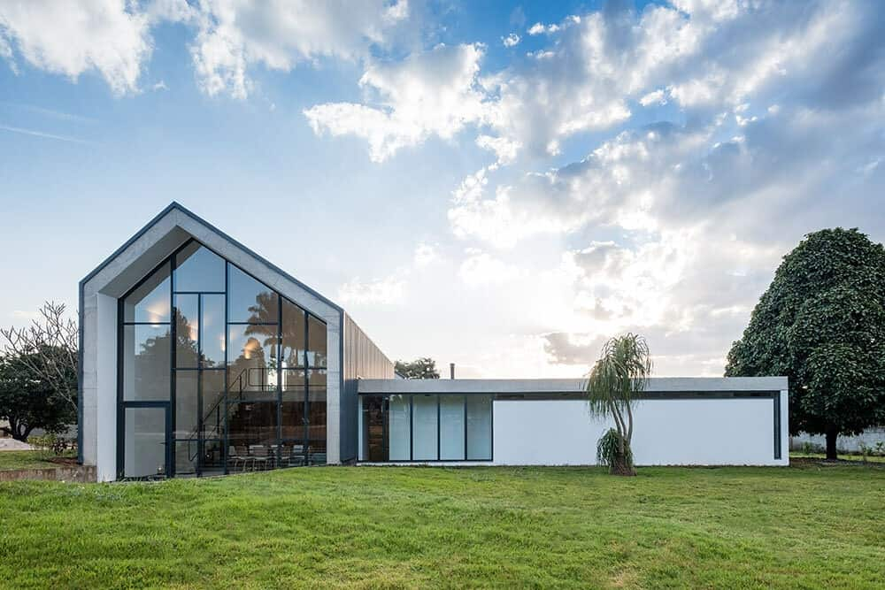 This is the daytime view of the front of the house depicting the bright exteriors that go well with the large glass wall and windows complemented by the grass lawn.