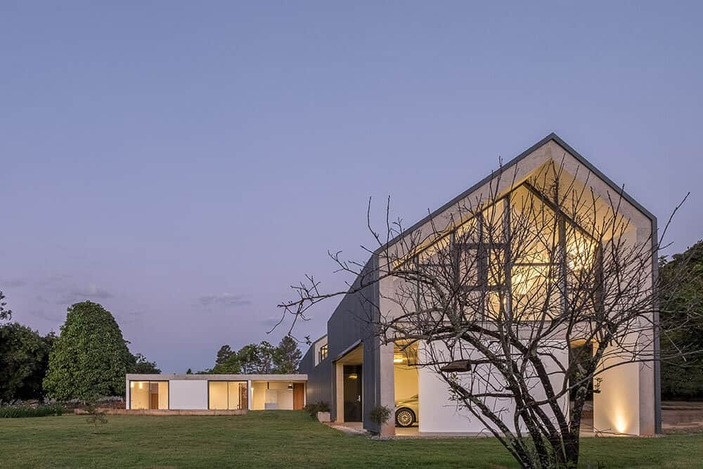 This is a nighttime look at the house featuring the warm glowing glass walls that go well with the surrounding grass lawns.