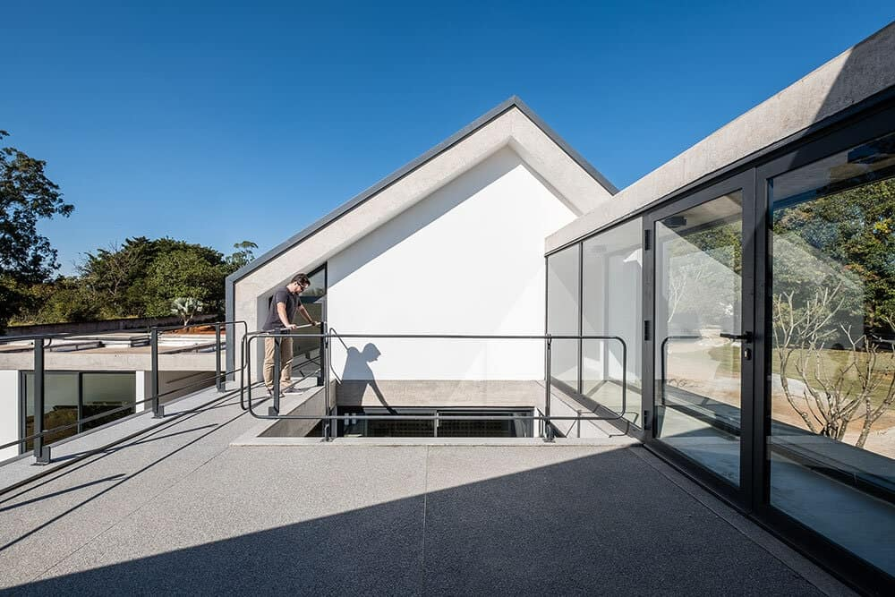 This is a close look at the rooftop open area of the house with a section that has glass walls.