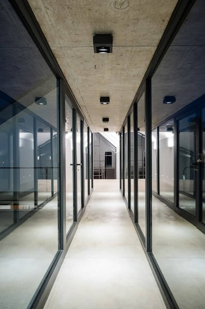 This is a hallway inside the house with glass walls on both sides and an industrial-style feel to its floor and ceiling.