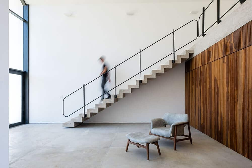 This is an interior look at the large hall with a staircase on the far wall and a simple arm chair and footstool in the middle.