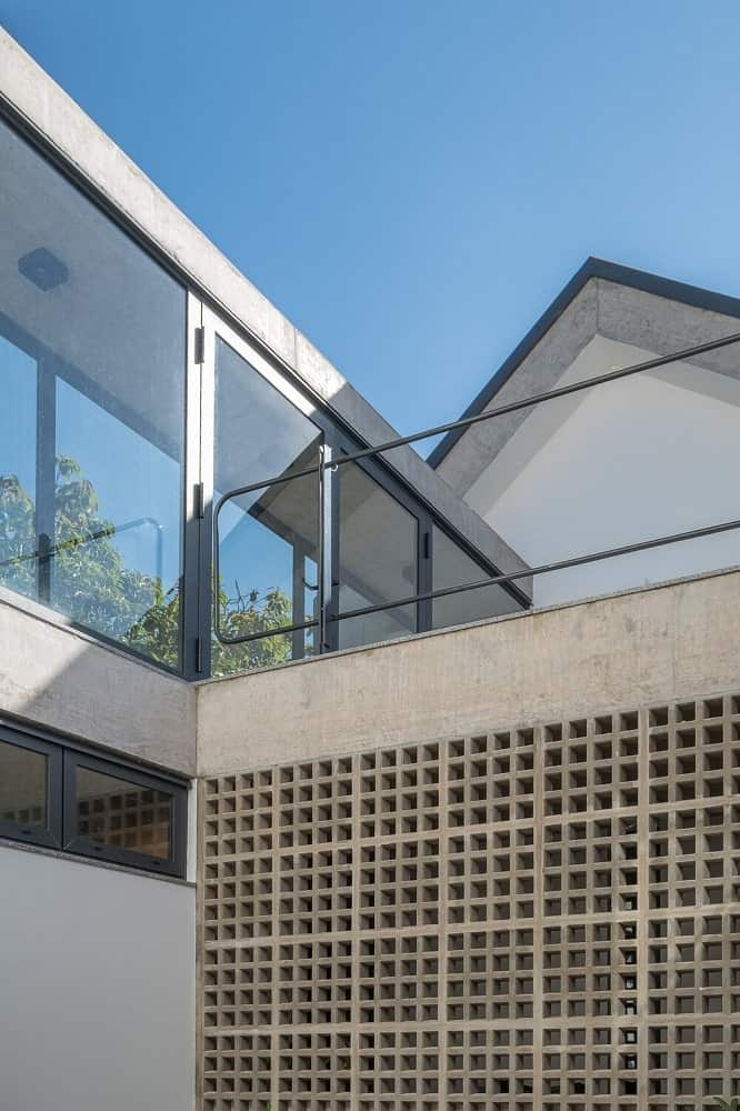 This is a close look at the exterior of the house showcasing the metal frames and glass walls.