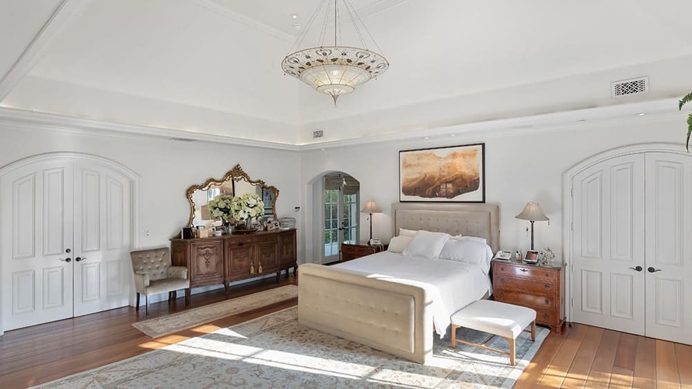 This bedroom has a consistent bright tone to its walls and cove ceiling that hangs a dome pendant light over the bed topped with a painting. Image courtesy of Toptenrealestatedeals.com.
