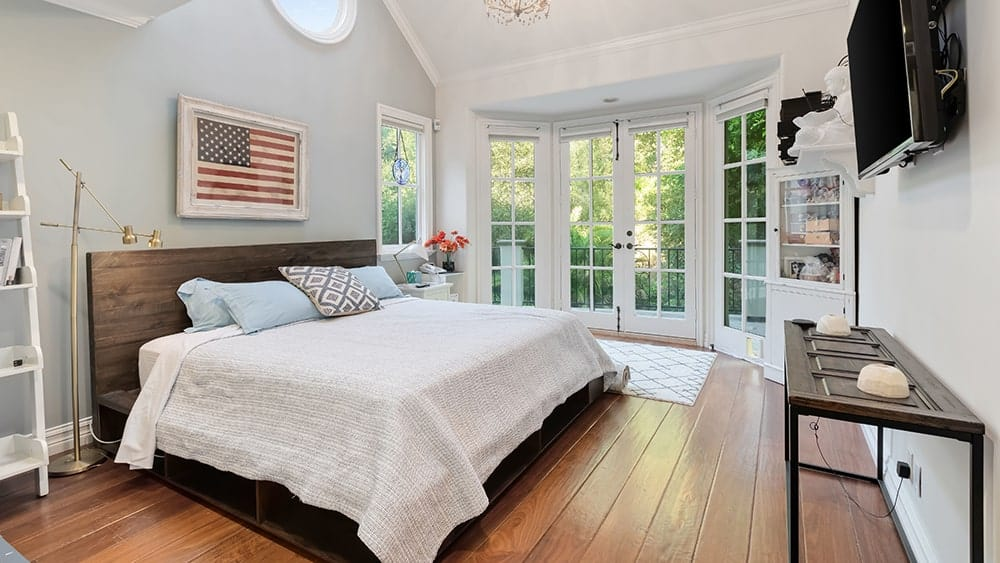 This other bedroom has a large bed that is illuminated by the large bow window on the far side with French-style windows and doors leading to the balcony. Image courtesy of Toptenrealestatedeals.com.
