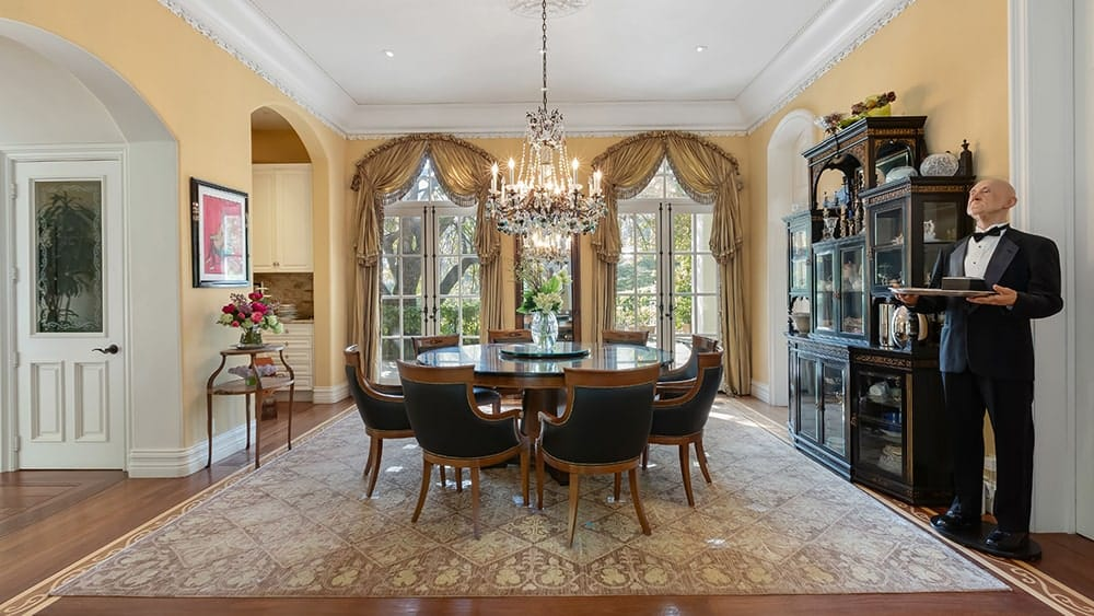 This is the formal dining room that has a alrge wooden round tab;e surrounded by matching chairs. These are then complemented by the chandelier and the large arched windows on the far side.Image courtesy of Toptenrealestatedeals.com.