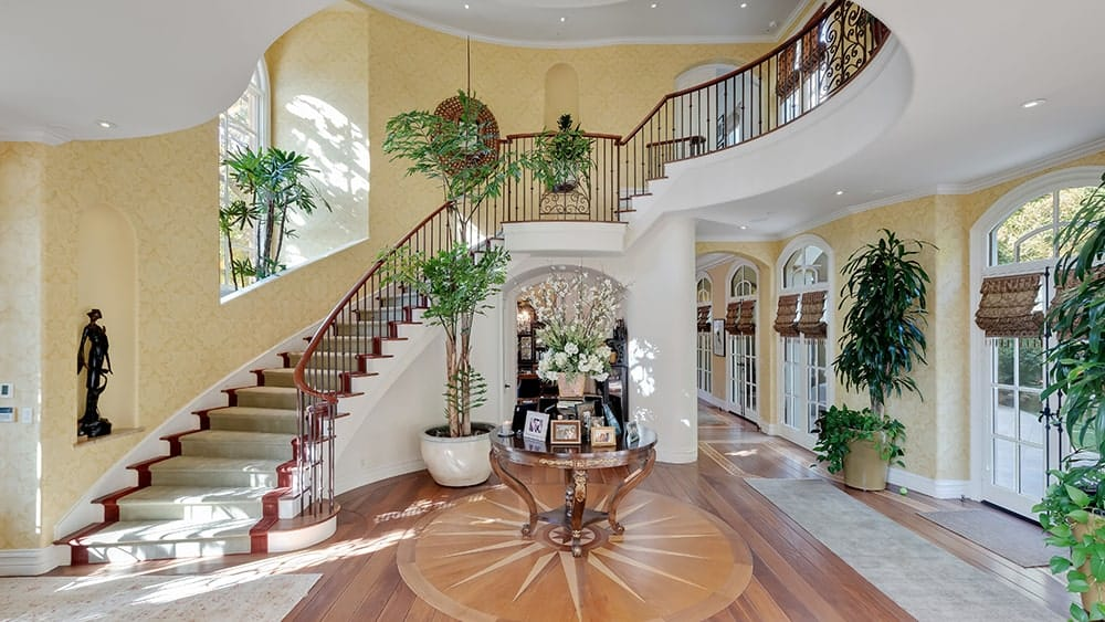 Upon entry of the house, you are welcomed by this foyer that has a large area, a large potted plant and a curved staircase illuminated by the large arched window. Image courtesy of Toptenrealestatedeals.com.
