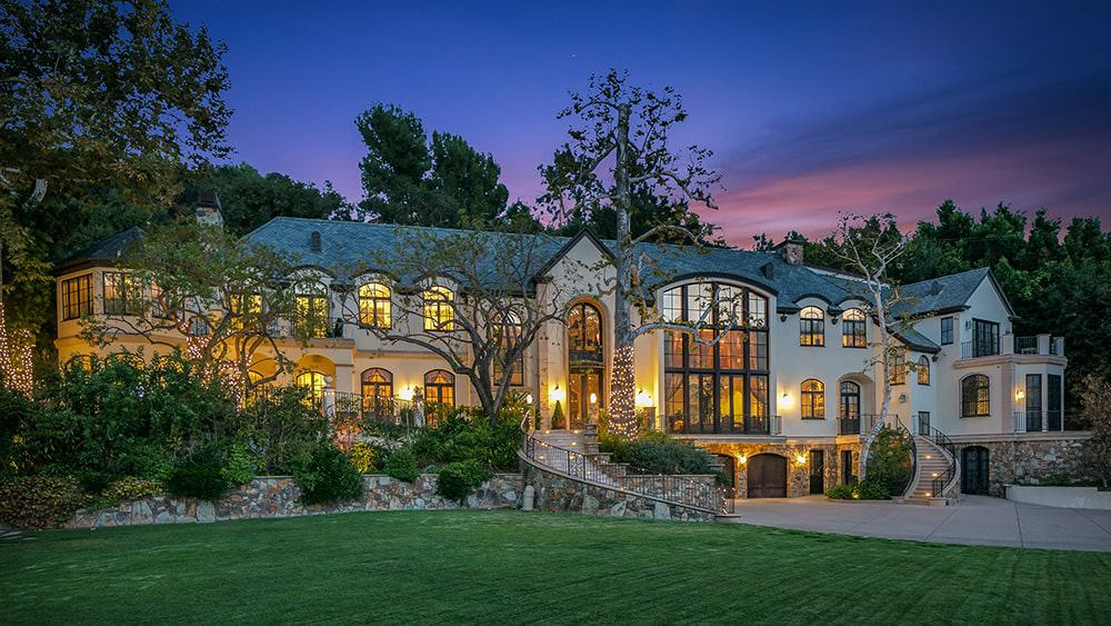 This is a nighttime view of the front of the house showcasing the many large glass windows and walls of the house that glows warmly from the interior lights that match the exterior lights complemented by the landscaping.Image courtesy of Toptenrealestatedeals.com.
