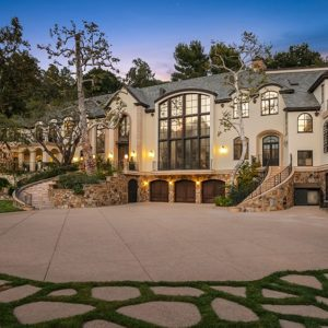 This is a view of the front of the house with a large courtyard and driveway leading to the three garage doors underneath the large glass wall. Image courtesy of Toptenrealestatedeals.com.