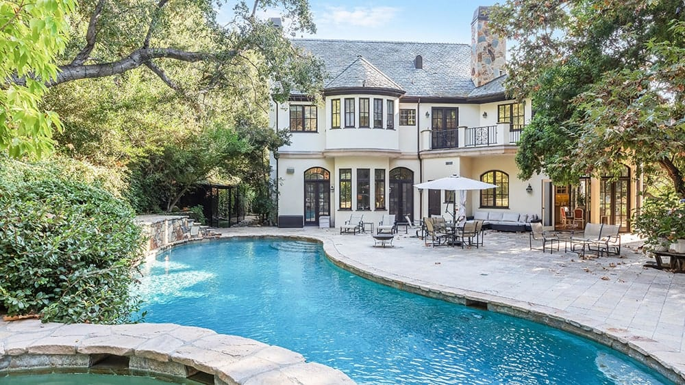 This is a look at the poolside area of the mansion with a alrge pool surrounded by lush landscaping and a few outdoor areas for relaxation adorned by the glass doors and windows of the house exterior. Image courtesy of Toptenrealestatedeals.com.