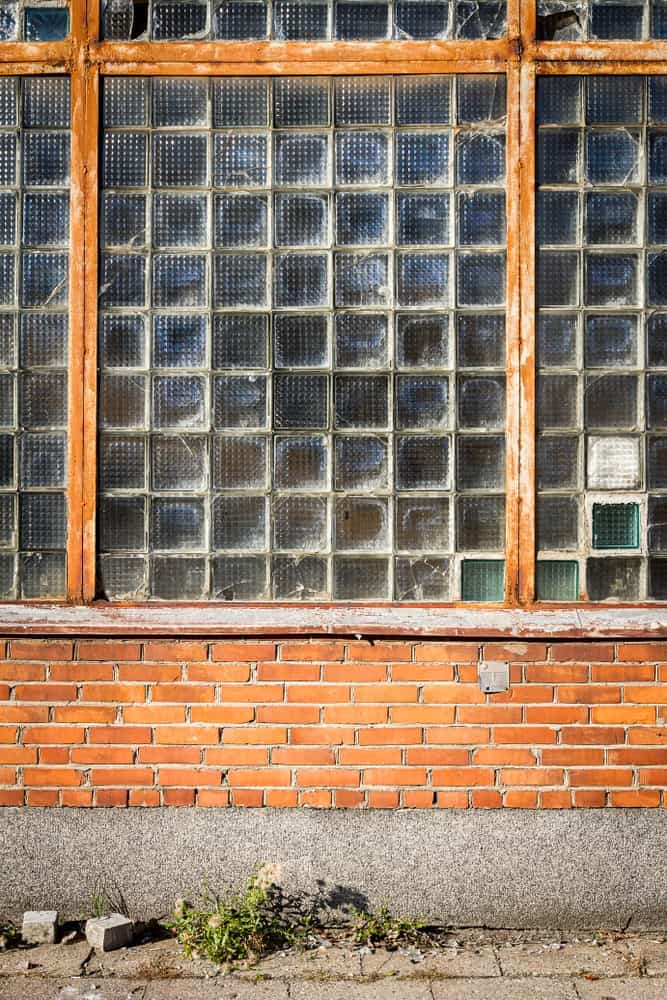 This is an exterior look at a glass block window above a red brick wall.