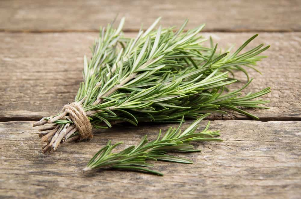 A cluster of rosemary on a wooden table.