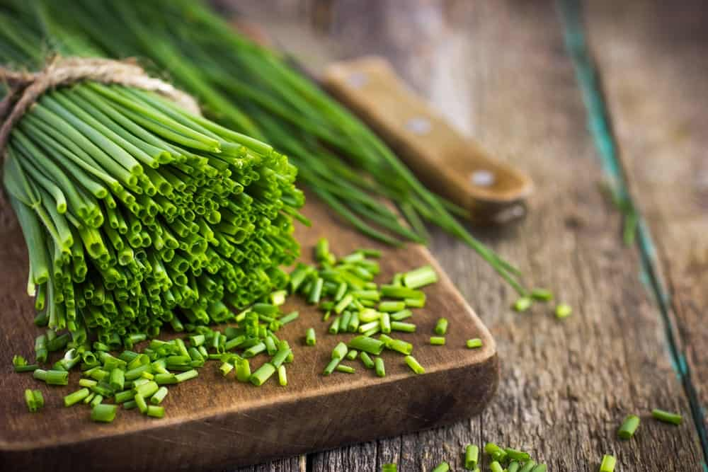 A bunch of chives being chopped on a board.