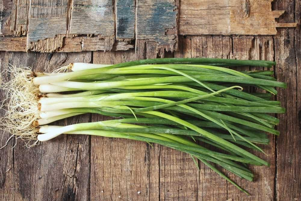 Green onion stalks on a wooden table.
