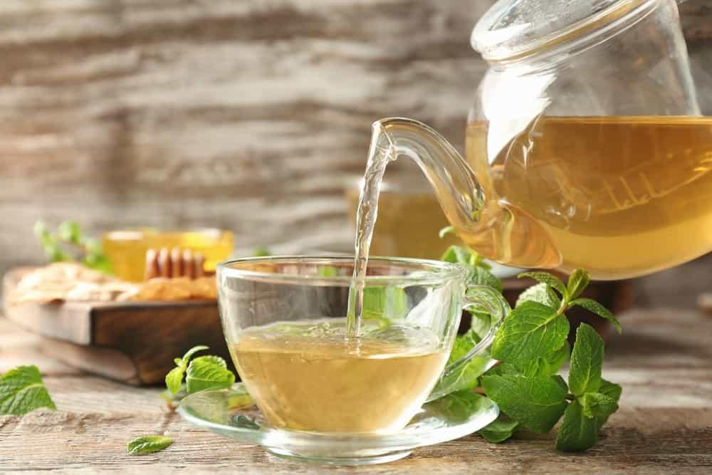 Lemon Balm tea being poured onto a glass cup.