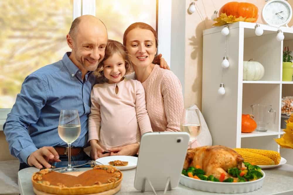 A family of three having a virtual thanksgiving.