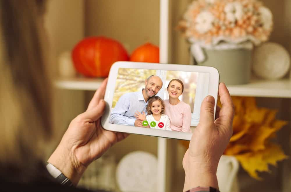 A woman having a virtual thanksgiving with a family of three.