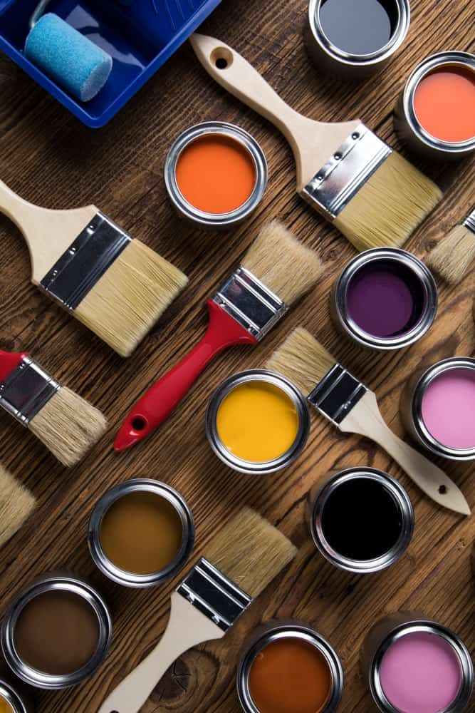 Brushes and various cans of paint on a wooden table.
