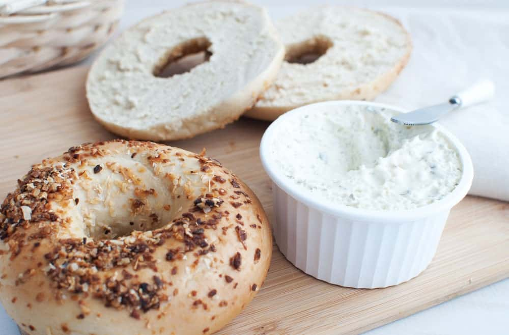 Cream cheese about to be applied onto pieces of bagel.