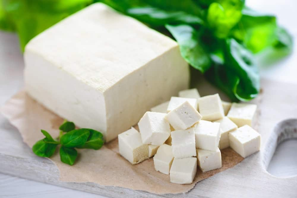 A large block of tofu cut up into cubes.