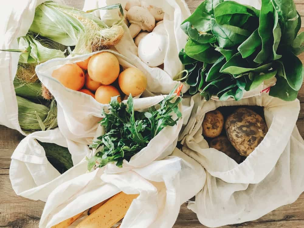 Fresh fruits and vegetables in eco-friendly reusable bags.