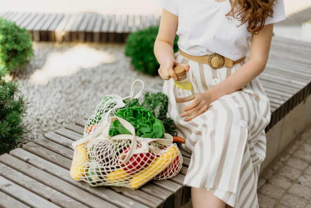 A woman sitting on a park bench with her groceries in an eco-friendly mesh bag.
