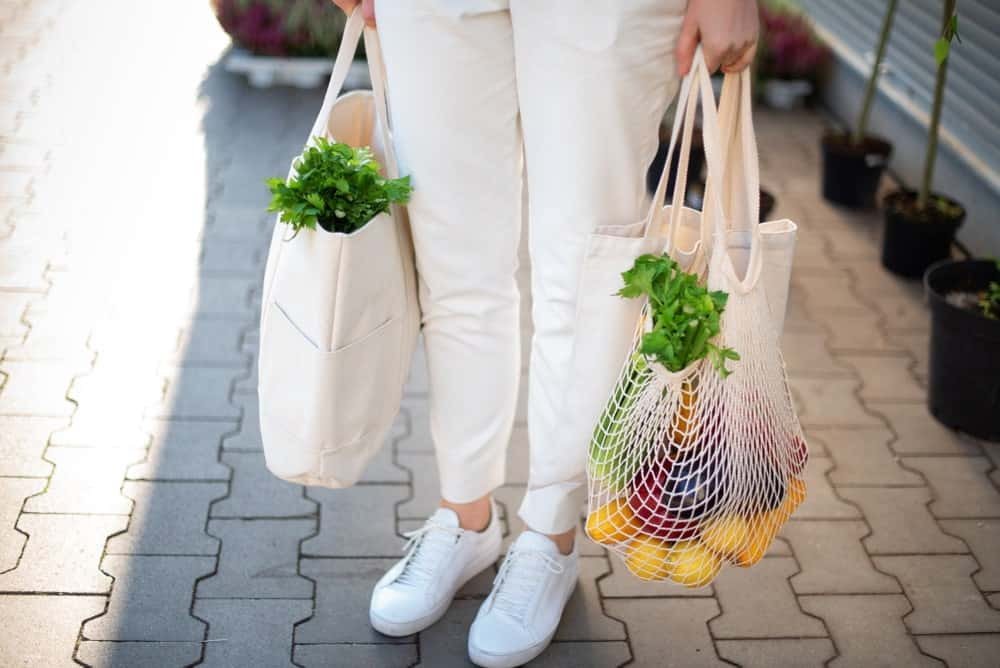 A woman carrying her groceries in eco-friendly reusable bags.