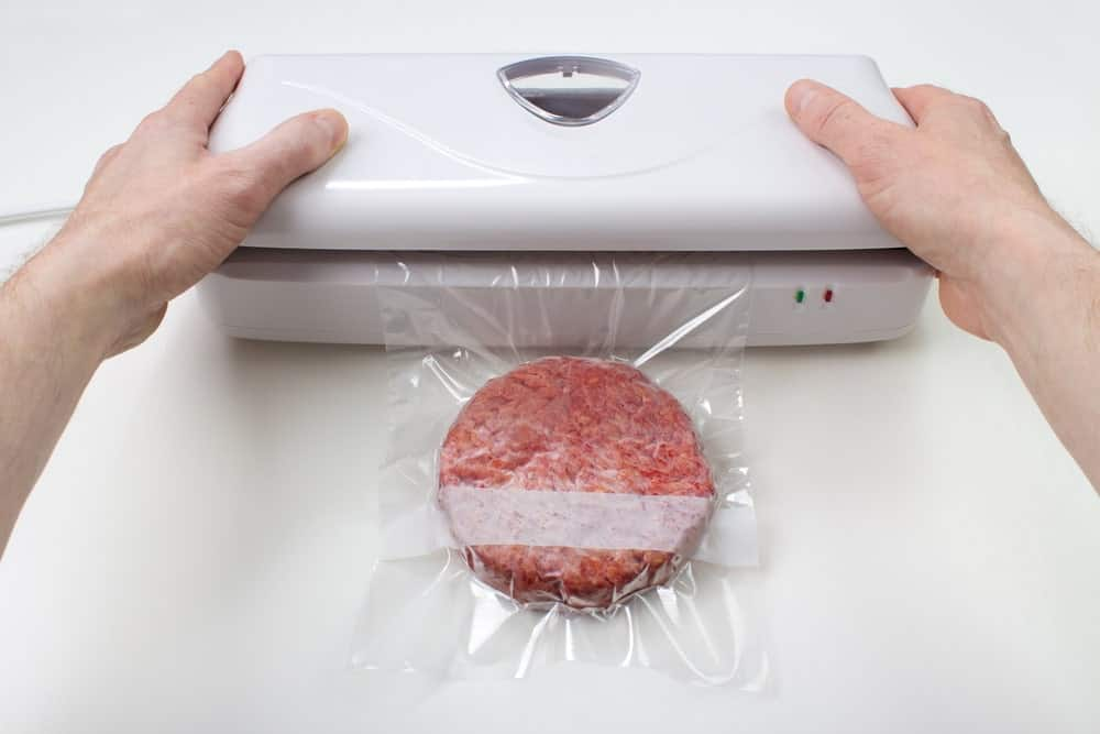 A raw burger patty being vacuum-sealed.
