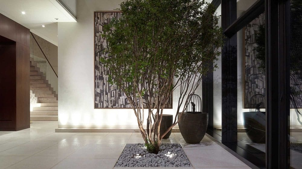 Upon entry, you are welcomed by this foyer that is adorned with a medium-sized tree, vases and a large wall-mounted artwork.