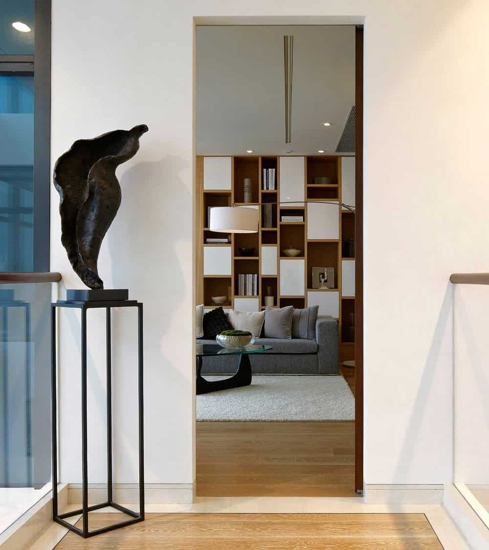 This is the second-floor landing with a hardwood flooring adorned with a sculpture on a pedestal.