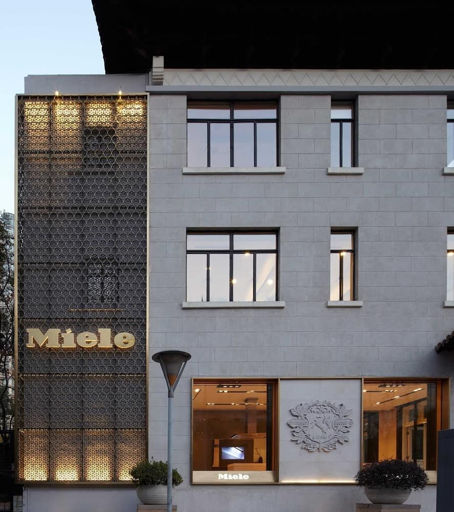This is an exterior look at the building with a section accented by patterned panels and paired with gray exterior tones.