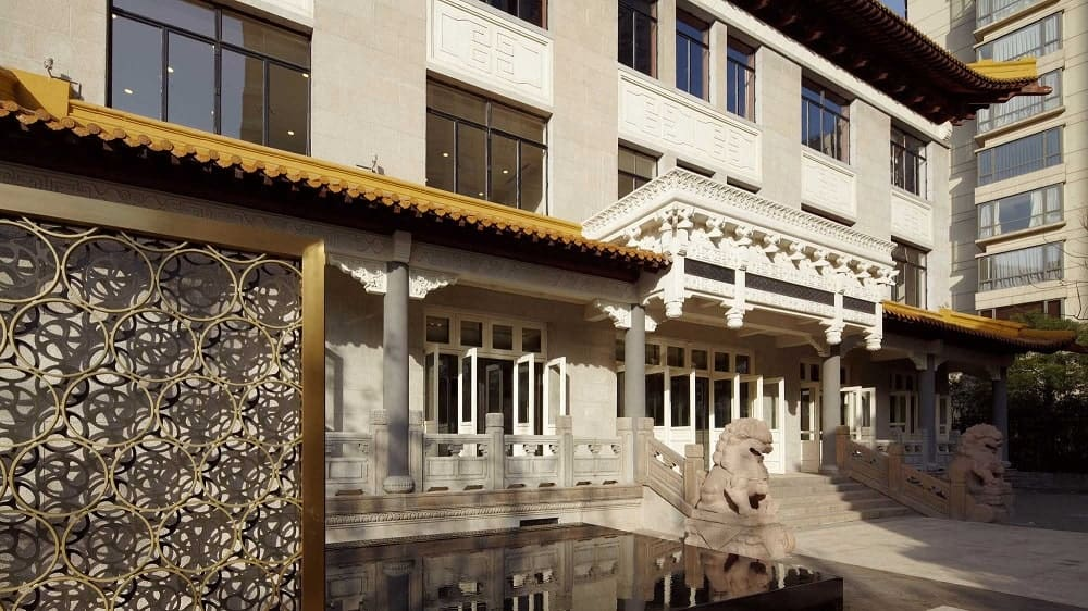 This is a close look at the main entrance of the building with a set of concrete steps flanked by lion statues.