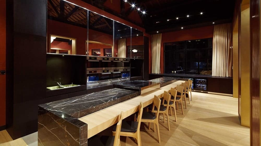 This is the large bar of the house with large black marble counter with an extension of wooden counters paired with chairs that match the tone of the flooring.