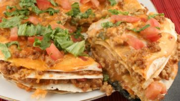 A plate of layered soft tacos with cheese toppings.