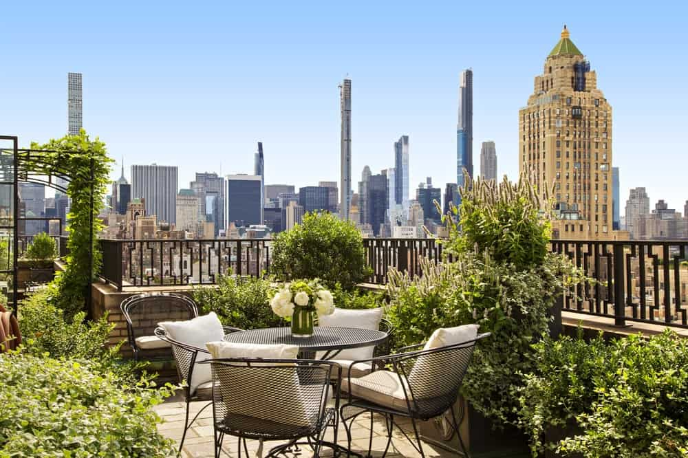 This corner of the large balcony terrace is fitted with an outdoor dining area that is adorned by various potted plants and a view of the city skyline. Image courtesy of Toptenrealestatedeals.com.