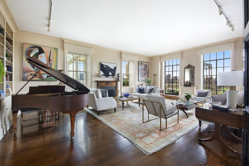 This is a view of the bright and airy living room that features a large grand piano on the opposite side from the window. Image courtesy of Toptenrealestatedeals.com.