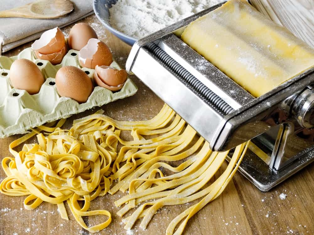 A pasta-cutting machine on a table with eggs and flour.