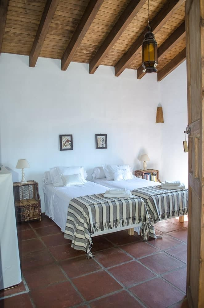 This bedroom has a couple of beds complemented by the side tables, beamed shed ceiling and terracotta flooring tiles.