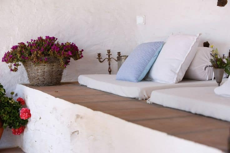On the side of the beds is a built-in concrete sitting area complemented by cushions and a basket of flowers.