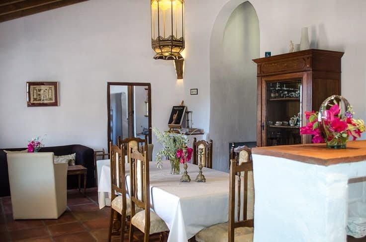 This is a closer look at the dining area of the great room with a rectangular dining table topped with a large lantern-like pendant light and surrounded by wooden chairs.
