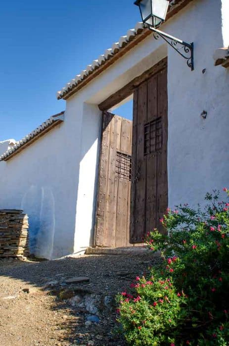 This is a close look at the outer wall of the property with a set of wooden doors topped with a set of clay tiles to match those of the house roof.