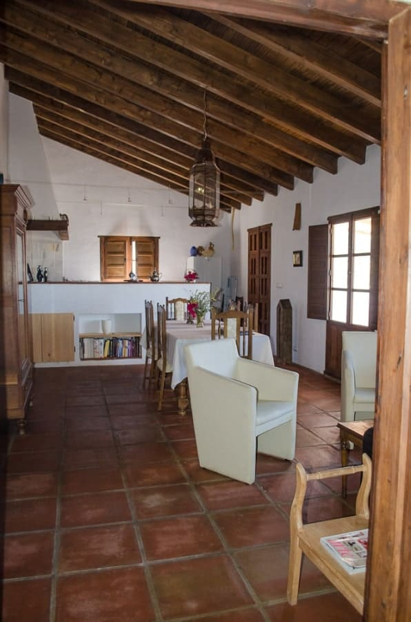 This is an interior view of the house showcasing a large open plan room with exposed wooden beams to its shed ceiling.