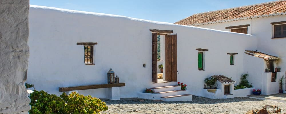 This is a full view of the outer wall of the property with a white tone to its exterior complemented by the windows and wooden doors as well as planters.