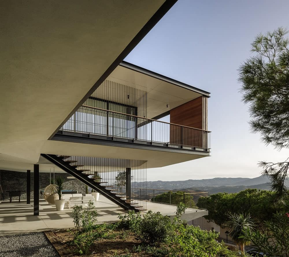 This is a look at the side of the house facing the sweeping view of the mountains maximized with a large balcony and a terrace at the ground level.