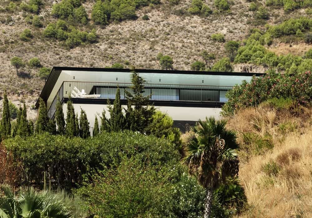 This is a look at the house from the vantage of the cliff showcasing the thick and lush landscaping that brings color to the exteriors of the house.