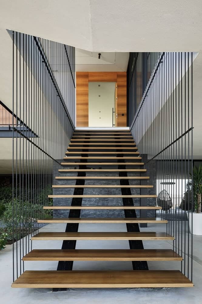 This is a closer look at the floating staircase that leads from the terrace to the balcony above with thin railings on the side.