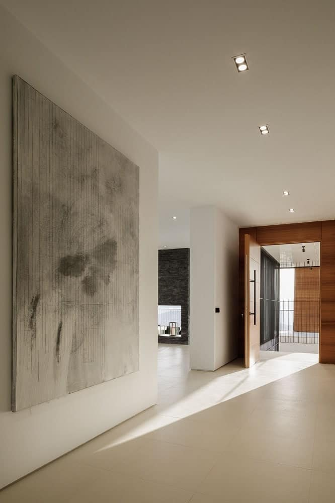 Upon entry of the house, you are welcomed by this simple and minimalist foyer that has a large gray painting on the side to complement the walls and ceiling.