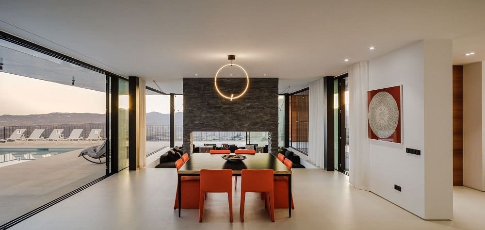 This is a close look at the dining area with a sleek dark rectangular dining table paired with brightly colored chairs that stand out against the light tone of the floor.