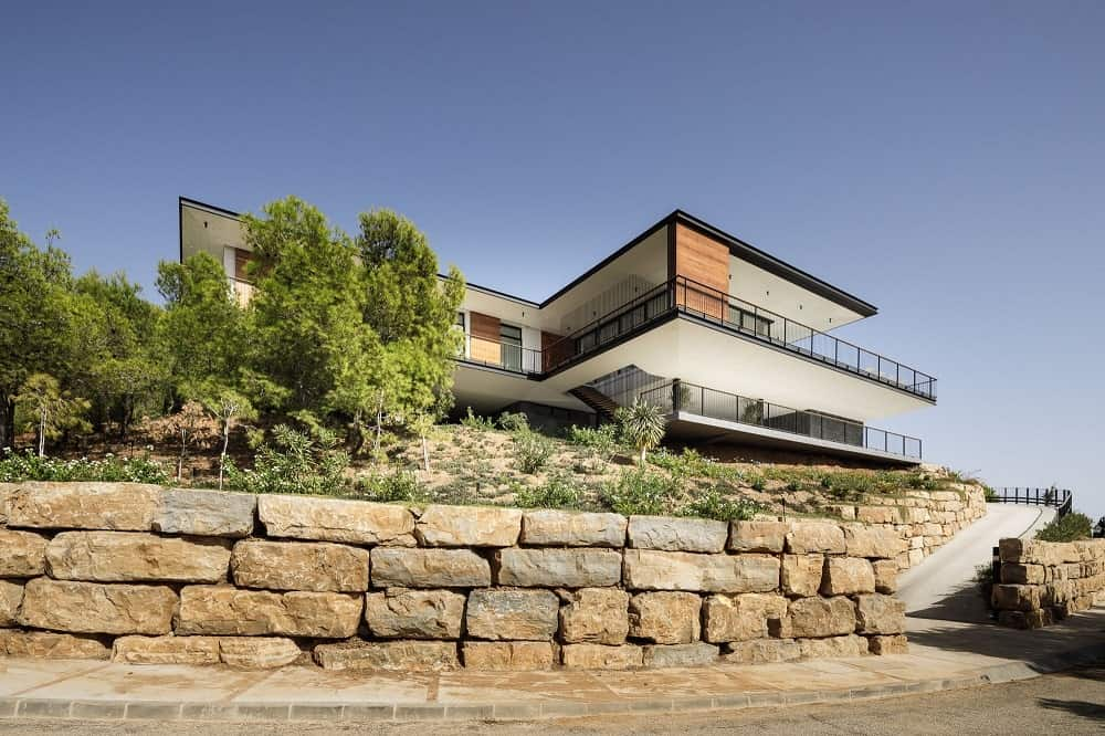 The house is also complemented by a large garden with grass, shrbs and trees bordered with large stone blocks.