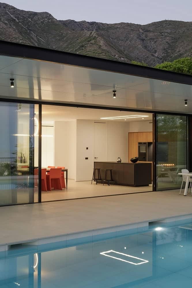 A few steps from the dining area is the modern kitchen and the large opening that leads to the poolside area.